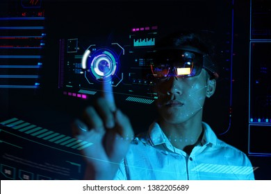 Young man try virtual reality glasses  hololens 1 in the dark room with advanced technology. Future technology concept. Face recognition.