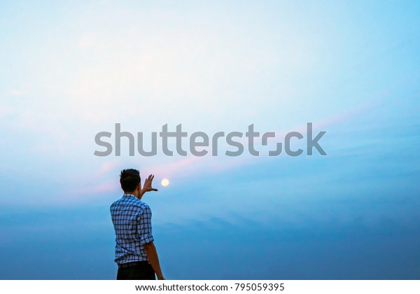 Young man trying to catch the moon before sunrise
