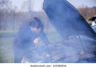 A young man is trying to fix the car that just broke down. He is checking what may have gone wrong with the car.