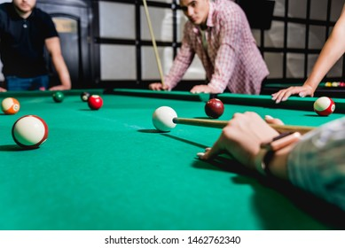 Young man trying to hit the ball in billiard. Pool background