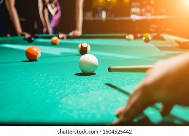 Young man trying to hit the ball in billiard. His friends on the background.