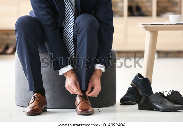 Young man trying on shoes in shop