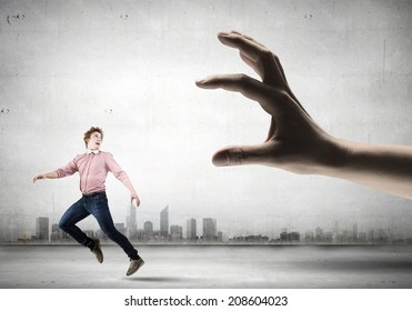 Young man trying to run away from big male hand