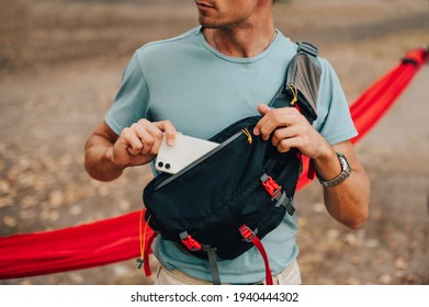 A young man in a T-shirt and a waist bag on his shoulder puts a smartphone in his pocket, close up
