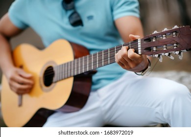 a young man in a turquoise shirt plays a Spanish guitar
