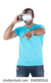 A young man in a turquoise T-shirt wearing a VR glasses smiling and raising his finger trying to touch something in the game, isolated on a white background.