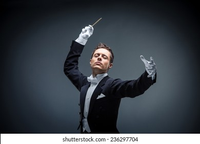 Young man in tuxedo conducting
