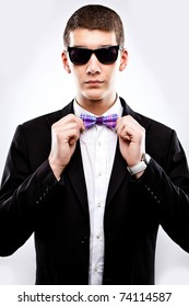 Young man in tuxedo fixing bow tie