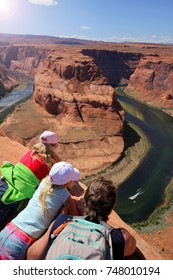 Young man and two girls laying on the edge of the cliff. Horse Horseshoe Band Canyon. Adventure and tourism concept