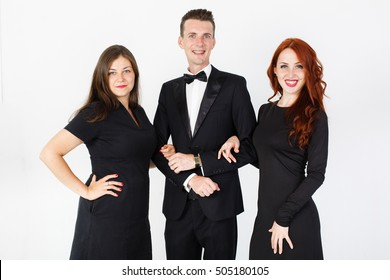 Young man and two women in black on a white background. Trio band of  actors performing on the stage. Smiling team of man and two women on white background with copy space
