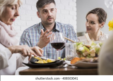 Young man and two women sitting beside table during family dinner