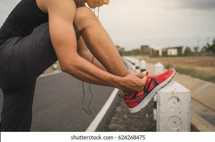 Young man tying his shoelaces before starting daily routine workout. Man doing exercises and warm up before run and Physical fitness test on bridge.