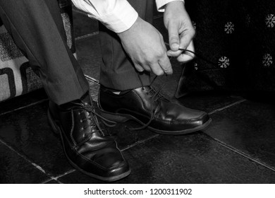 Young man tying his shoes.