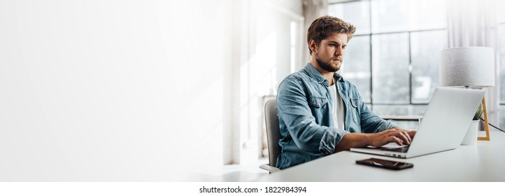 Young man typing on laptop. Modern businessman at sunny office. Freelancer at work. Blogger or journalist writing new article. Copy space for text