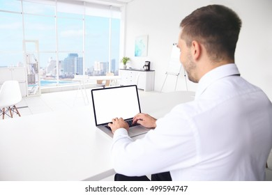 Young man typing on laptop at office