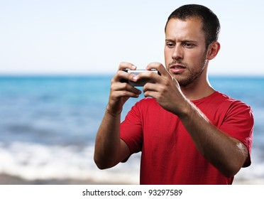 young man typing on a mobile phone against a beach background