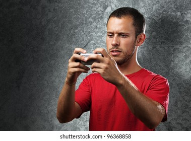 young man typing on mobile phone against a grunge wall