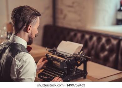 Young man typing on a retro typewriter close-up