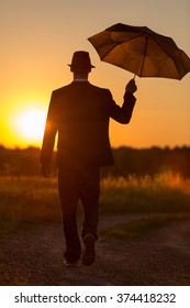 A young man with umbrella and hat walks into the sunset