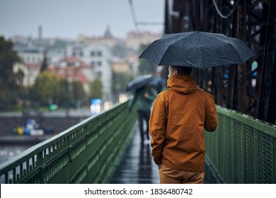 Young man with umbrella is walking on bridge during heavy rain. Gloomy day in Prague, Czech Republic