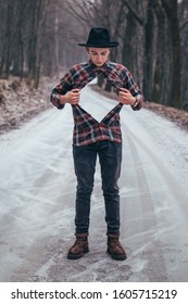 Young man unbuttons shirt and shows empty space. Boy acting like superhero and tearing off shirt on chest. Invisible man in clothing and with visible face stands on snow covered road in winter forest