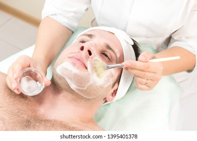 A young man is undergoing a mask treatment in a beauty salon spa.