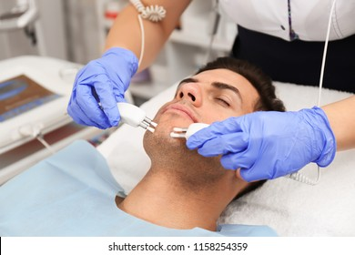 Young man undergoing microcurrent therapy in beauty salon