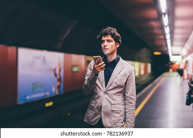 young man in the underground using smart phone - technology, waiting, commuting concept