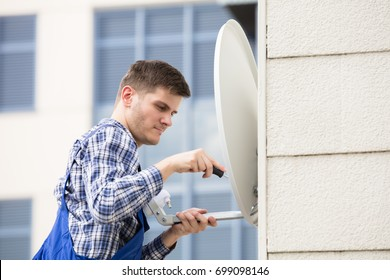 Young Man In Uniform Fitting TV Satellite Dish On Wall