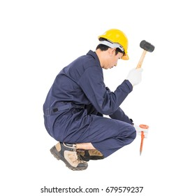 Young man in uniform sit and holding hammer was nailed to a cold chisel, Cut out isolated on white background