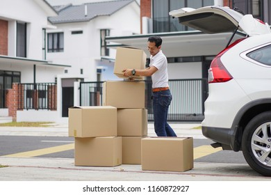 Young man unloading boxes from car trunk