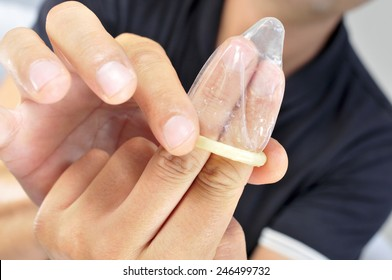 a young man unrolling a condom in his fingers