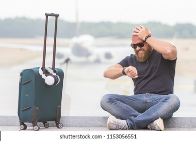Young man is upset, angry and disappointed because of a canceled flight -  concept of a man watching his smartwatch and being late for meeting because of air company strike or protests