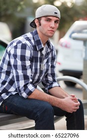 Young man in an urban lifestyle fashion pose sitting on a street bench wearing a hat.