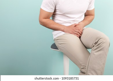 Young man with urological problems suffering from pain on color background