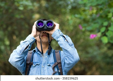 Young Man use of the binocular at forest