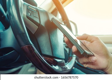 Young man use the telephone to send text messages to girlfriends while driving .Dangerous driving while typing text message.