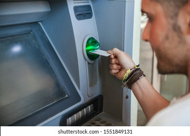 Young man uses the atm to withdraw cash from the bank