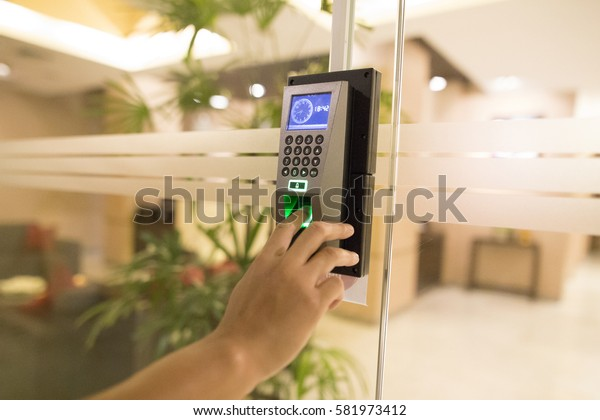 Young man uses finger push down for scan finger to access electronic door control