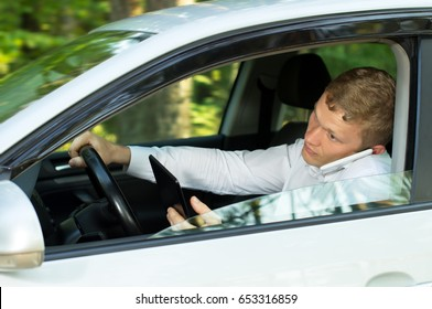 Young man uses  the phone behind the wheel of a car, creating an emergency situation