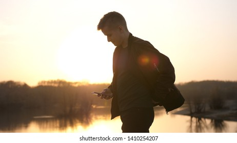 Young man uses smart phone at beautiful sunset on the beach.