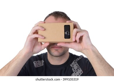 Young man uses virtual reality (VR cardboard) isolated on white background