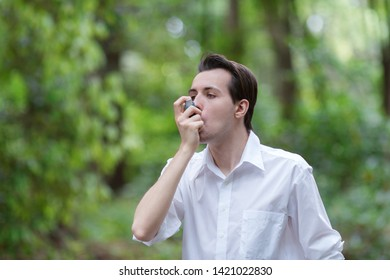 Young man is using a asthma inhaler