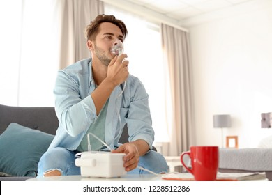 Young man using asthma machine at home. Space for text