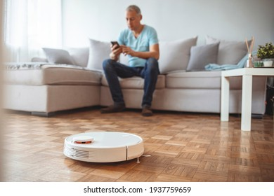 Young man using automatic vacuum cleaner to clean the floor, controling machine housework robot. Happy Man Lying On Sofa Operating Robotic Vacuum Cleaner With Remote Control