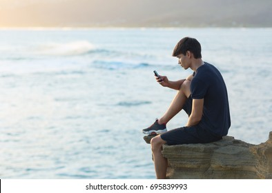 Young man using a cellphone on top a ocean cliff during sunset.