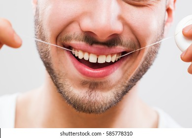 Young man is using dental floss to clean his teeth.