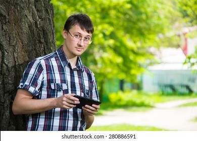 Young man using digital tablet portrait outdoors