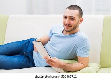Young man using digital tablet at his home.Man using digital tablet