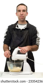 A young man using an electric beater to mix up some cookie batter, isolated against a white background